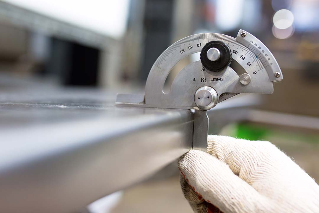 An engineer measuring steel with a measurement device