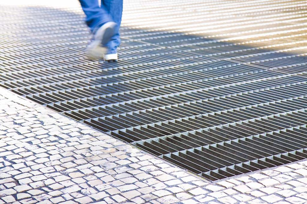 A metal grill walkway covering a ventilation shaft